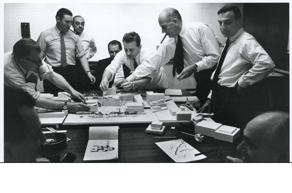 Metropolitan Opera architect Wallace Harrison (with cigar) and fellow architects around working model of Lincoln Center, 1958